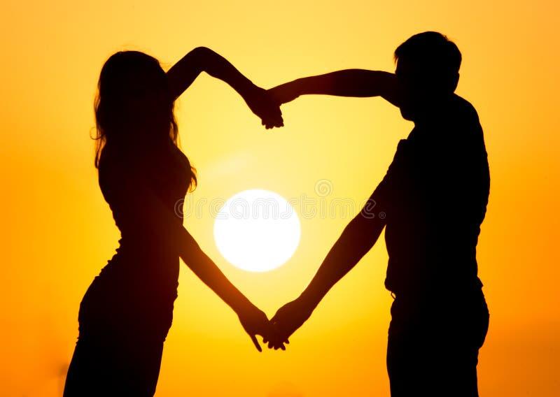 Silhouette d'un type et d'une fille au coucher du soleil images stock