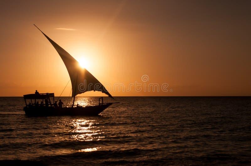 Silhouette d'un voilier au coucher du soleil dans un océan tranquille image stock