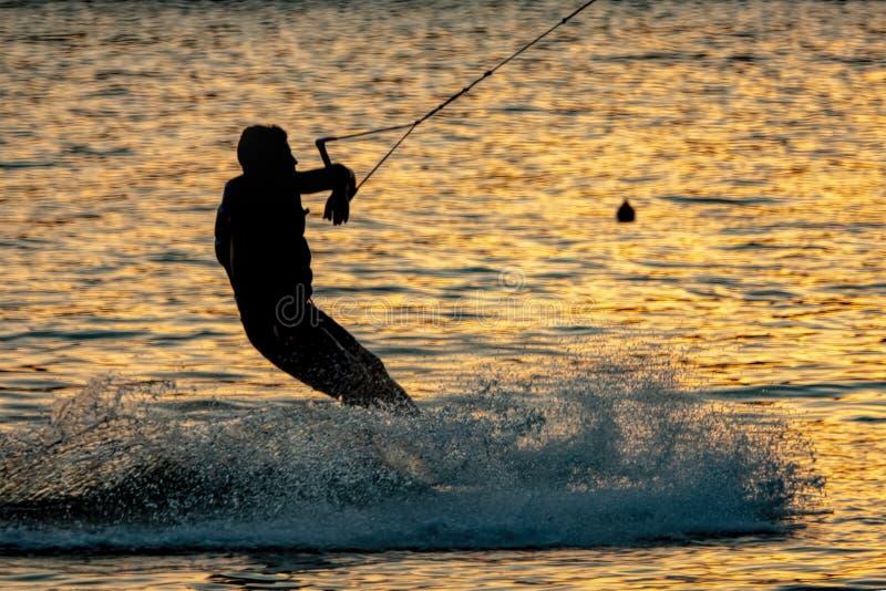 Silhouette d'un wakeboarder au coucher du soleil photo stock
