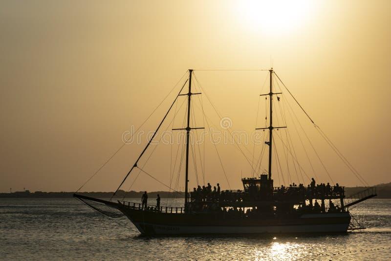 Silhouette d'un yacht en mer contre le coucher de soleil À bord du yacht sont les silhouettes des personnes images libres de droits