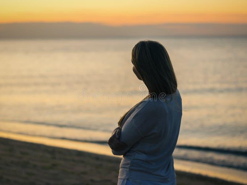 Silhouette d'une belle femme sur le fond du coucher de soleil de soirée photographie stock