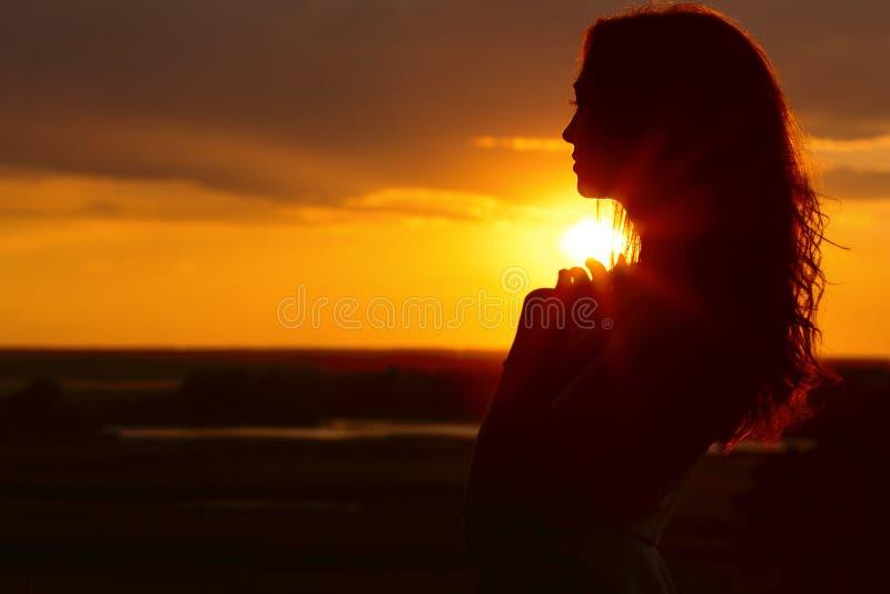 Silhouette d'une belle fille au coucher du soleil dans un domaine, profil de visage de jeune femme sur la nature photographie stock