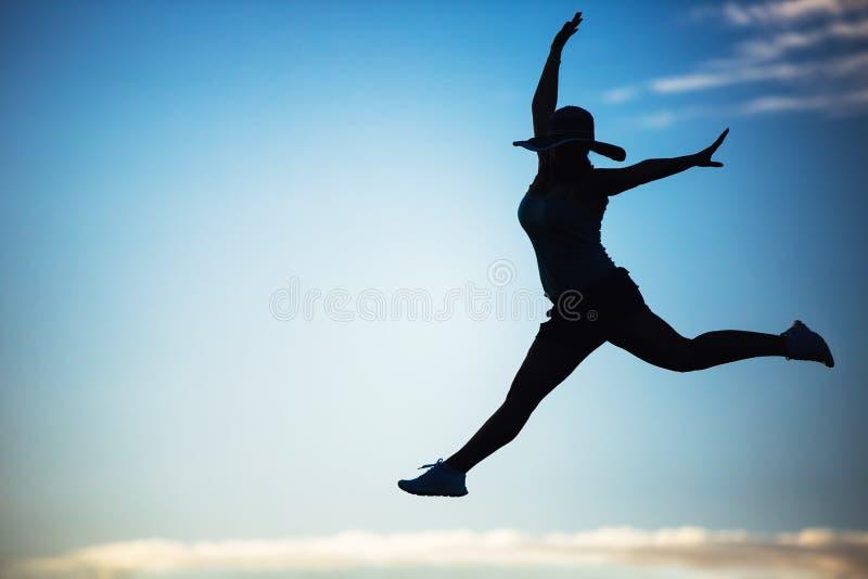 Silhouette d'une belle fille sautant par-dessus le coucher du soleil photos stock