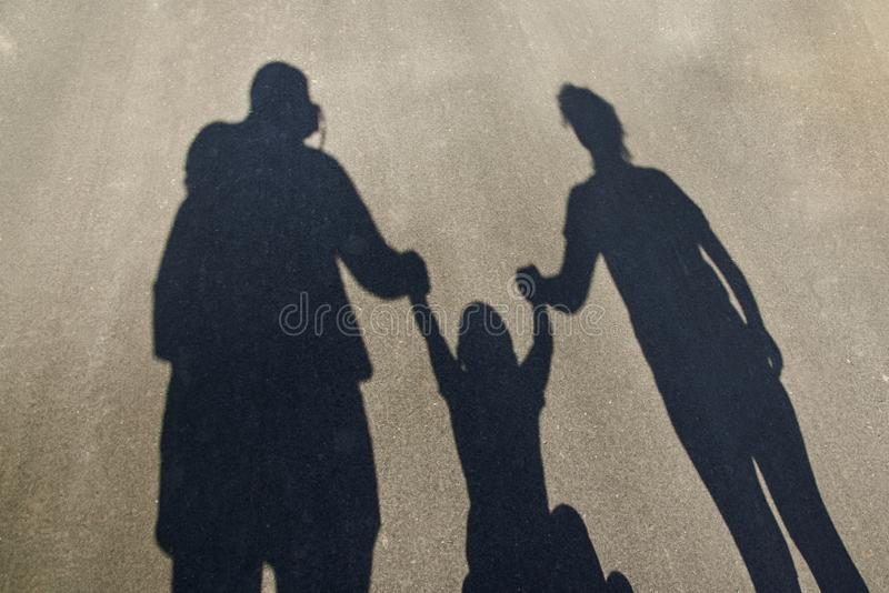 Silhouette d'une famille sur le trottoir : papa, maman et bébé tenant des mains image libre de droits