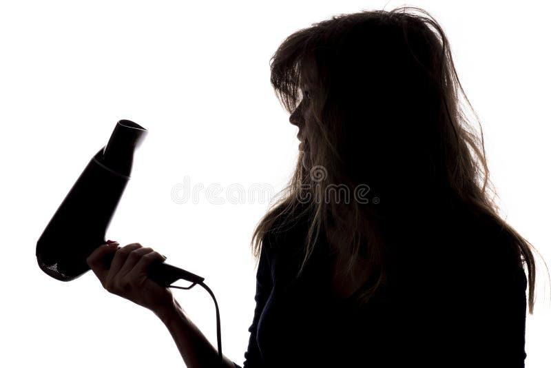 Silhouette d'une femme avec les cheveux embrouillés et endommagés avec un marais dans sa main, un concept de beauté et des soins  image stock