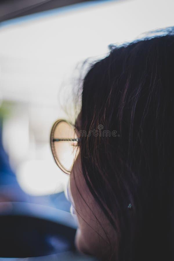 Silhouette d'une femme dans des lunettes de soleil avec l'espace de copie et le fond de bokeh image libre de droits