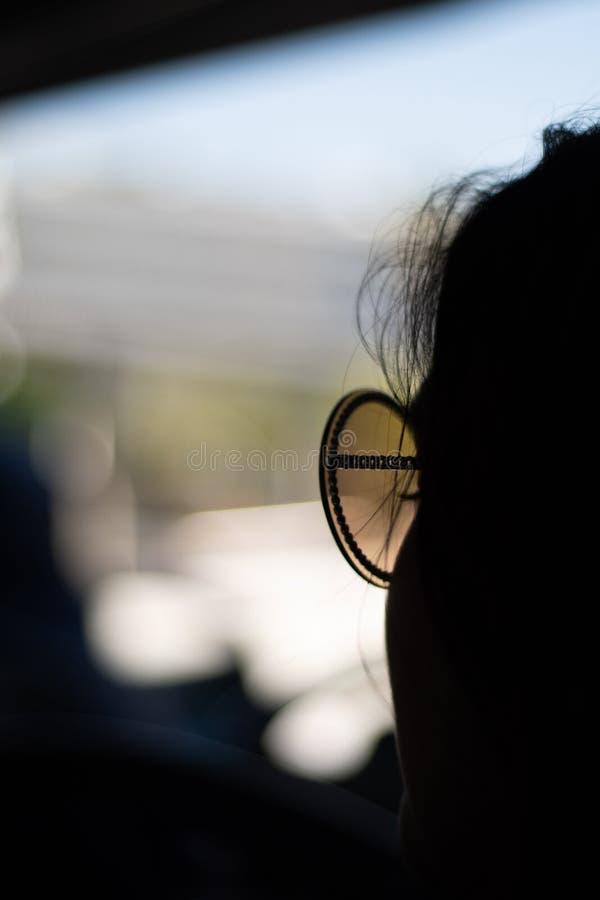 Silhouette d'une femme dans des lunettes de soleil avec l'espace de copie et le fond de bokeh photo stock