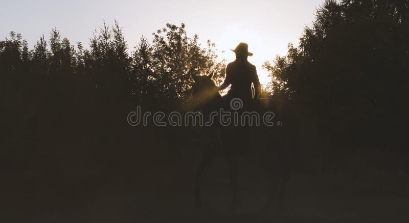 Silhouette d'une femme dans le chapeau de cowboy montant un cheval - coucher du soleil image libre de droits