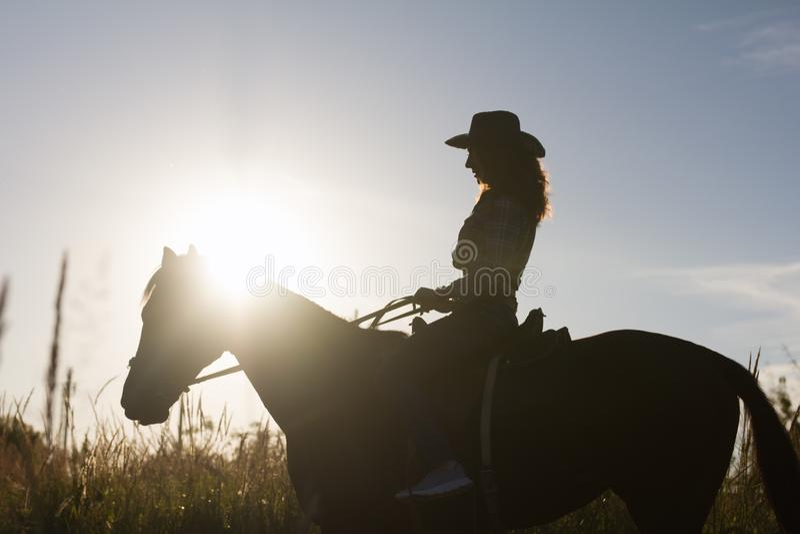 Silhouette d'une femme dans le chapeau de cowboy montant un cheval - coucher du soleil ou lever de soleil, horizontale photographie stock libre de droits