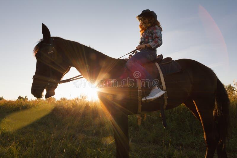 Silhouette d'une femme dans le chapeau de cowboy montant un cheval - coucher du soleil ou lever de soleil, horizontale images libres de droits
