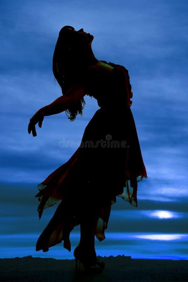 Silhouette d'une femme dans un dos de penchement de manière de robe photo stock