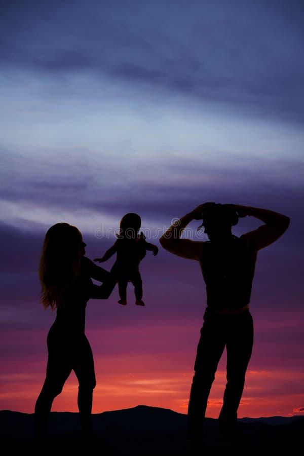 Silhouette d'une femme donnant son bébé photo stock