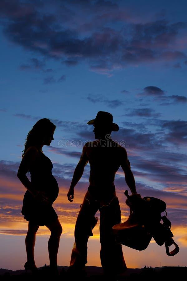 Silhouette d'une femme enceinte et d'un cowboy avec une selle photographie stock libre de droits
