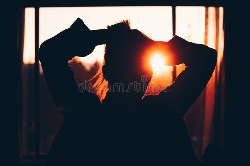 Silhouette d'une femme fixant ses cheveux devant une fenêtre avec le coucher du soleil à l'arrière-plan images stock
