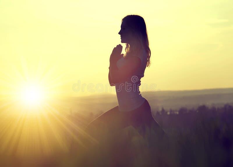 Silhouette d'une femme méditant sur un pré photos libres de droits