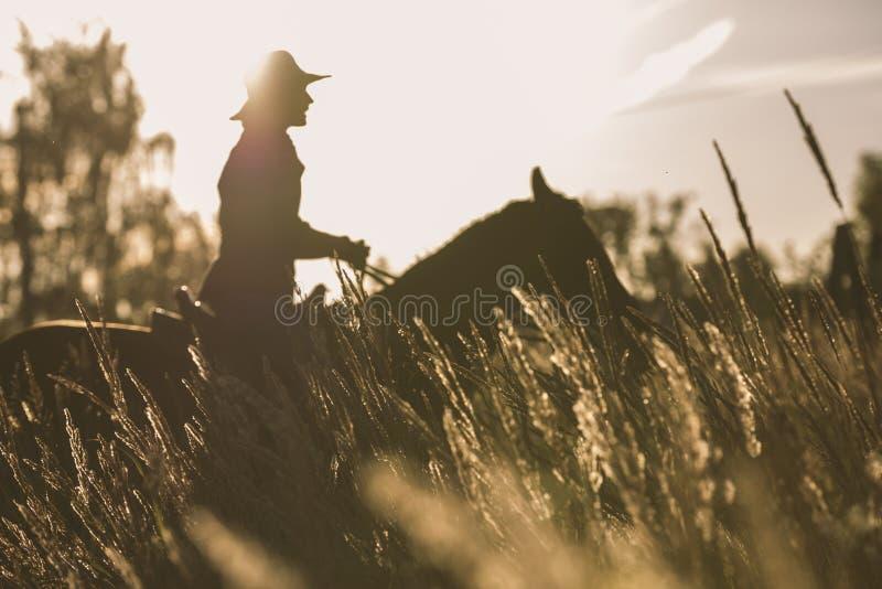 Silhouette d'une femme montant un cheval - coucher du soleil ou lever de soleil photographie stock libre de droits