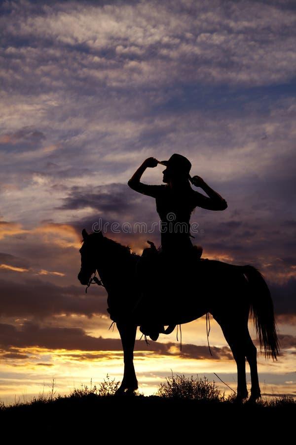 Silhouette d'une femme s'asseyant sur des mains d'une selle sur le chapeau photo stock