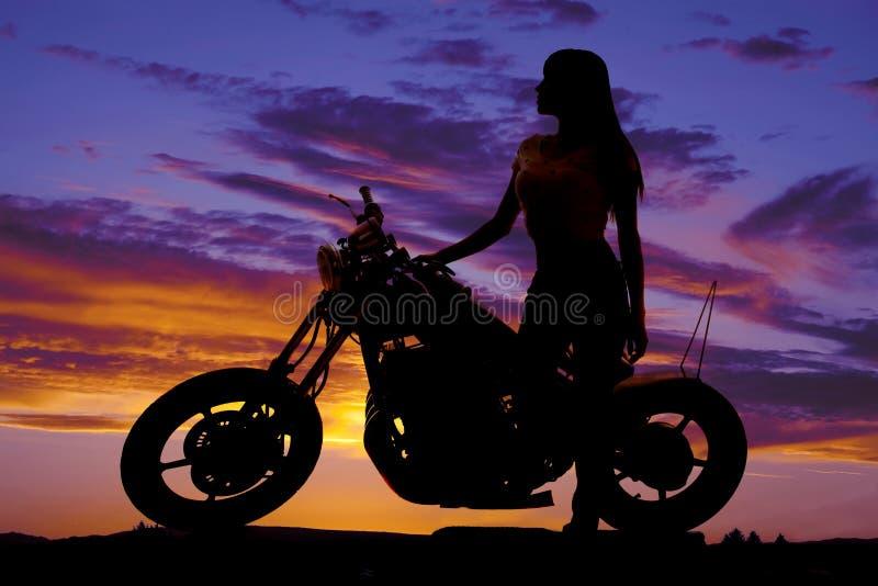 Silhouette d'une femme se tenant prêt une moto regardant en avant photos libres de droits