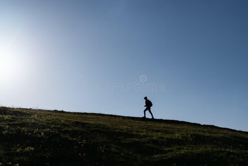 Silhouette d'une femme seule marchant au coucher du soleil sur une colline images libres de droits