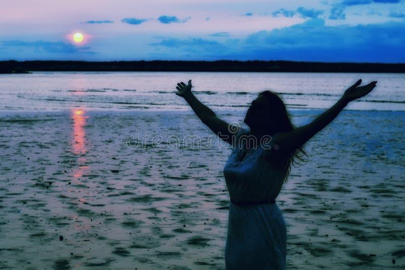 Silhouette d'une femme soulevant des mains à l'océan image libre de droits