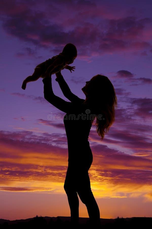 Silhouette d'une femme supportant son bébé image stock