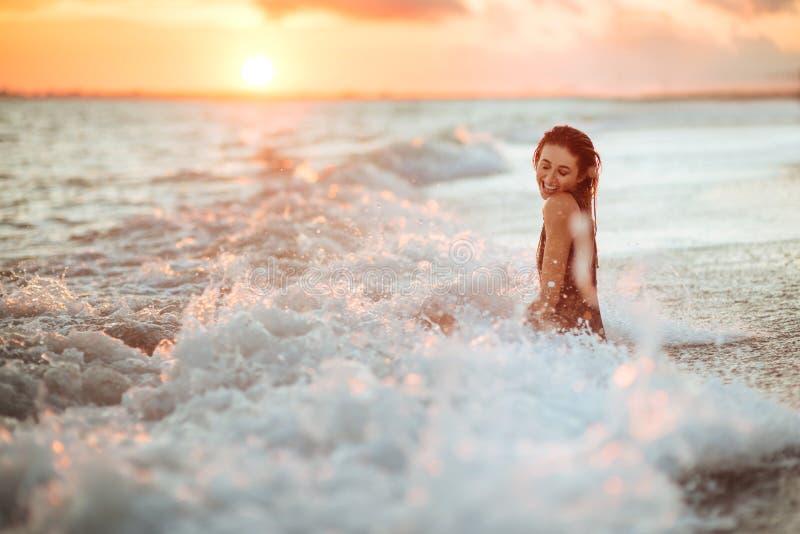 Silhouette d'une fille dans l'eau au coucher du soleil image libre de droits