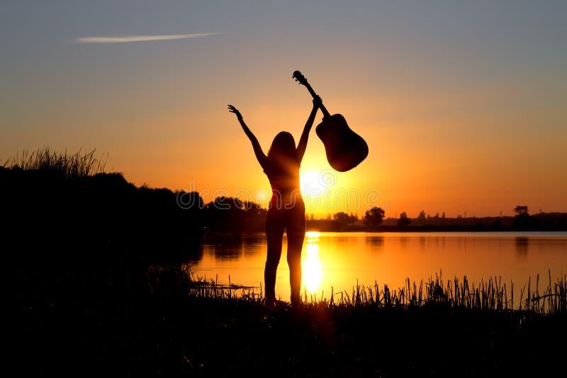 Silhouette d'une fille heureuse avec une guitare sur la nature photos libres de droits