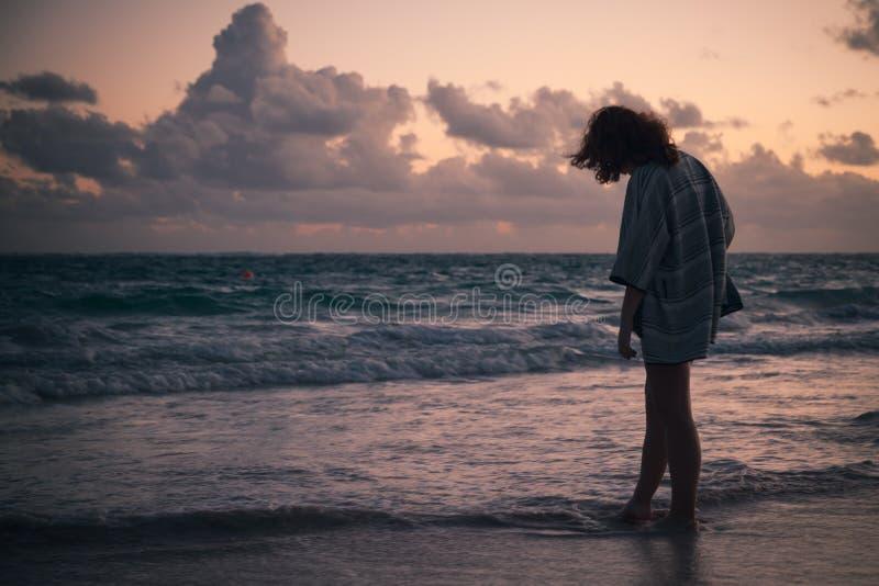 Silhouette d'une fille marchant sur la côte d'océan image libre de droits