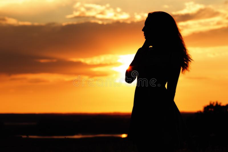 Silhouette d'une fille rêveuse dans un domaine au coucher du soleil, une jeune femme appréciant la nature images stock