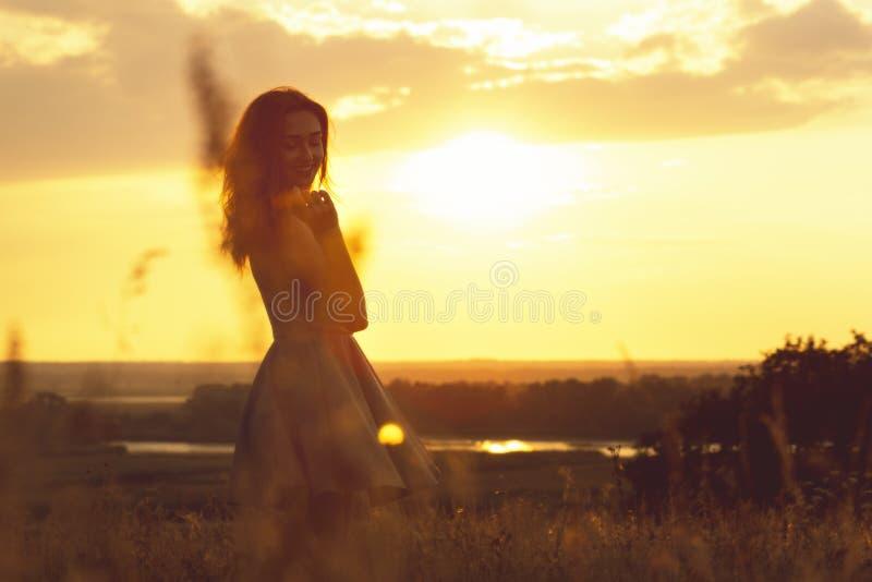 Silhouette d'une fille rêveuse dans un domaine au coucher du soleil, une jeune femme appréciant la nature images libres de droits