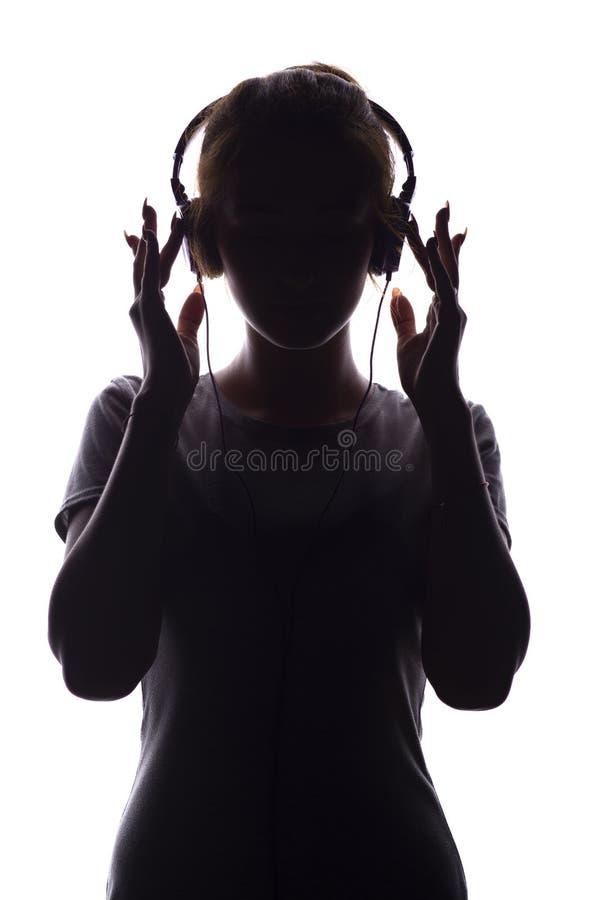Silhouette d'une fille romantique écoutant la musique dans des écouteurs, jeune femme détendant sur un fond blanc, concept de photographie stock