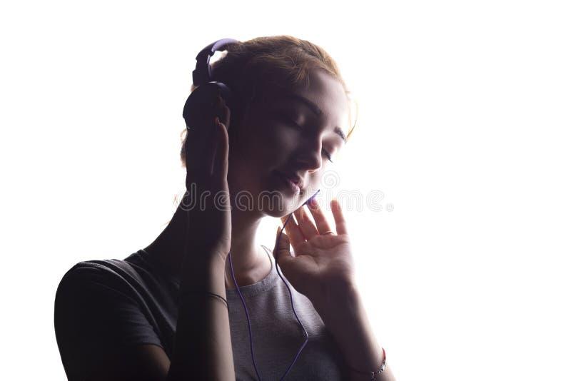 Silhouette d'une fille romantique ?coutant la musique dans des ?couteurs, jeune femme d?tendant sur un fond d'isolement blanc, co images stock