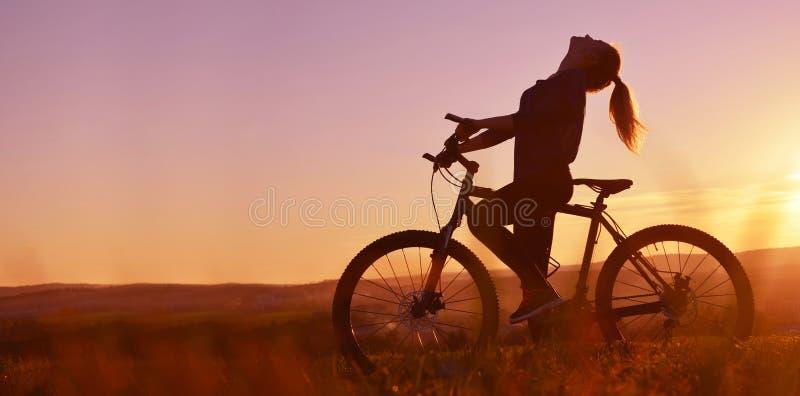 Silhouette d'une fille sur une bicyclette dans le coucher du soleil photos stock