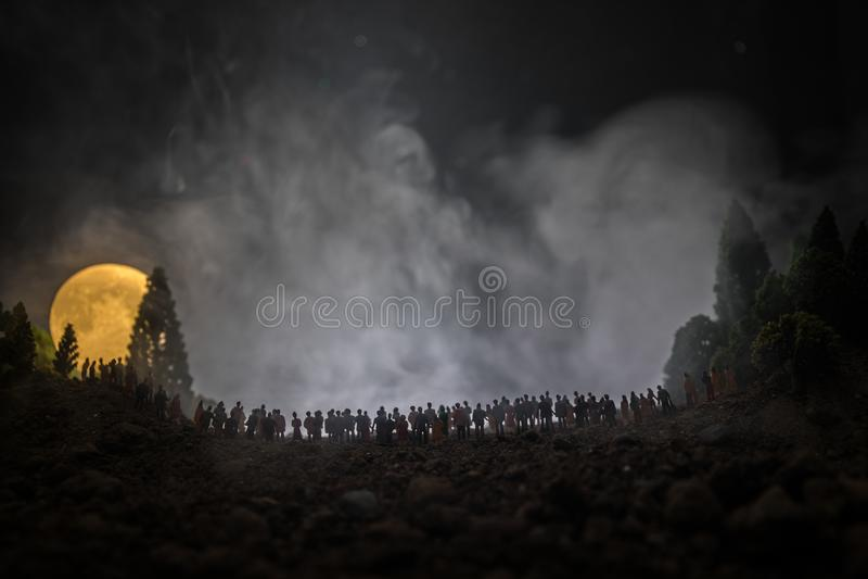 Silhouette d'une grande foule des personnes dans la forêt la nuit observant à la grande pleine lune en hausse Fond décoré avec l' photographie stock libre de droits