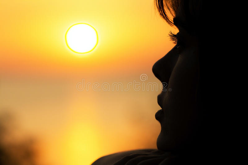 Silhouette d'une jeune femme au coucher du soleil photos stock