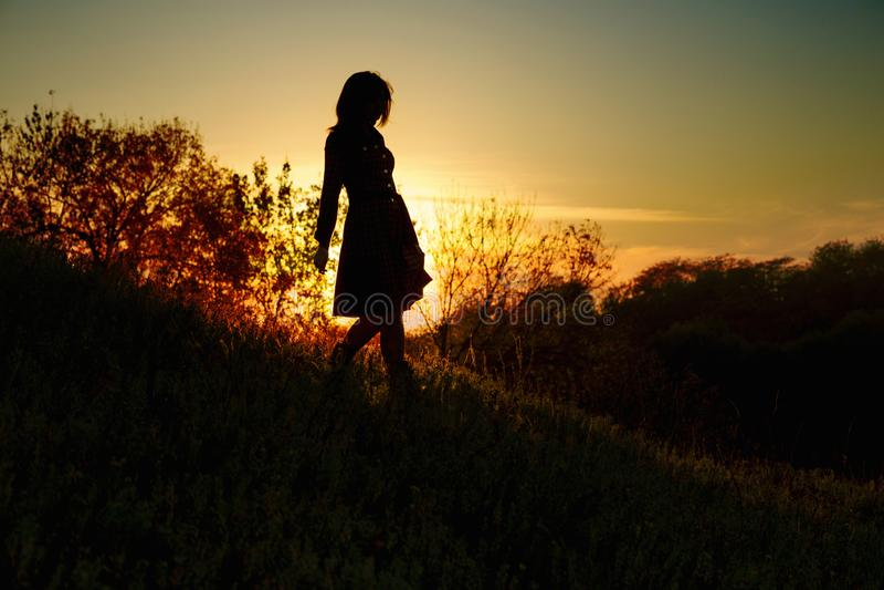 Silhouette d'une jeune femme descendant d'une colline au coucher du soleil, une fille marchant pendant l'automne dans le domaine image stock