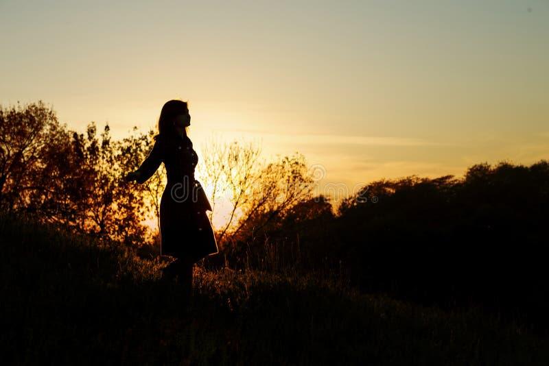 Silhouette d'une jeune femme descendant d'une colline au coucher du soleil, une fille marchant pendant l'automne dans le domaine images libres de droits