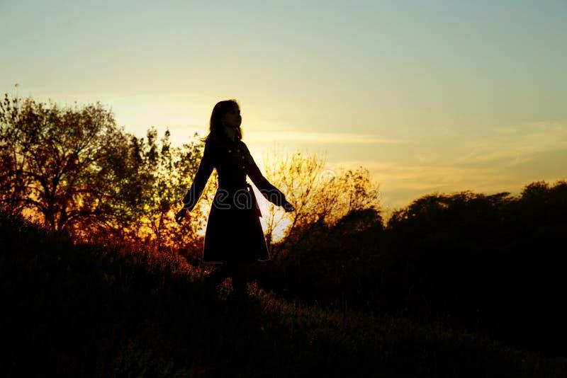 Silhouette d'une jeune femme descendant d'une colline au coucher du soleil, une fille marchant pendant l'automne dans le domaine photo libre de droits