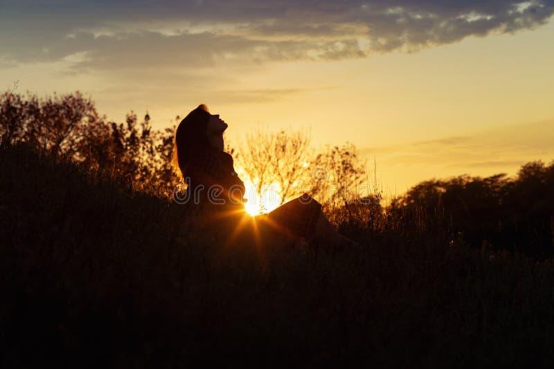 Silhouette d'une jeune femme s'asseyant sur une colline au coucher du soleil, une fille marchant pendant l'automne dans le domain photos stock