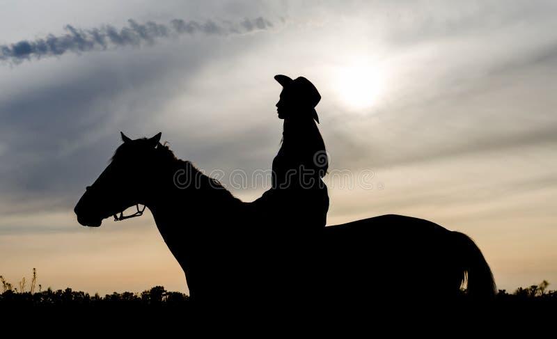 Silhouette d'une jeune fille avec un chapeau sur un cheval sur le fond du ciel de coucher du soleil image libre de droits