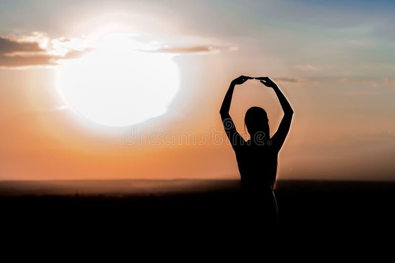 Silhouette d'une jeune fille sur le fond de coucher du soleil photos libres de droits