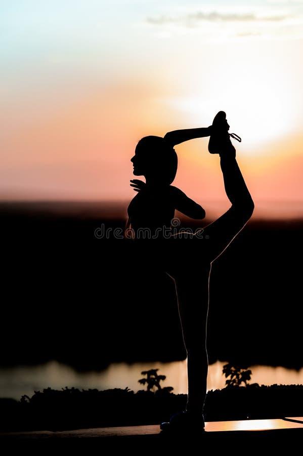 Silhouette d'une jeune fille sur le fond de coucher du soleil photographie stock