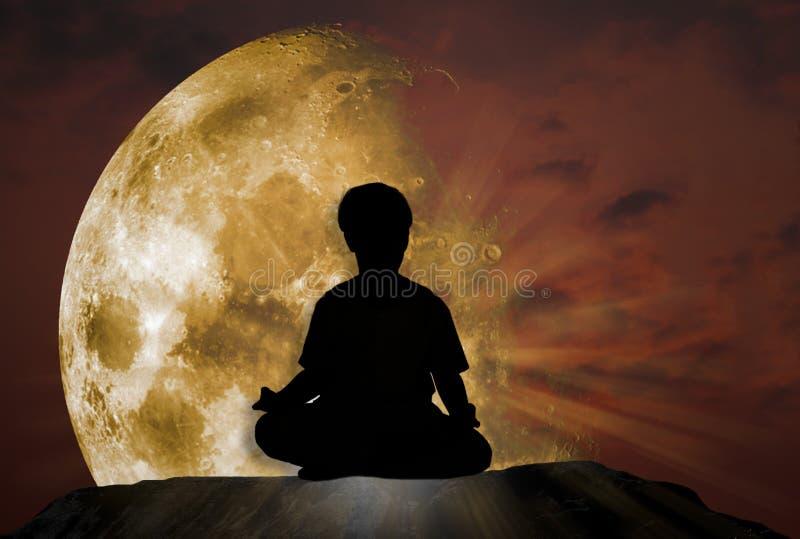 Silhouette d'une méditation de détente d'homme en nature, sur une falaise rocheuse en pente avec un ciel crépusculaire photographie stock libre de droits