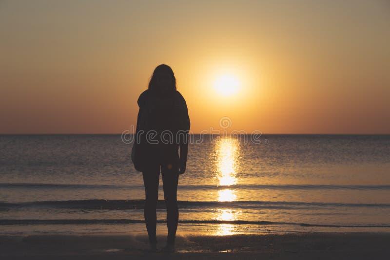 Silhouette d'une position de femme sur la plage photo stock