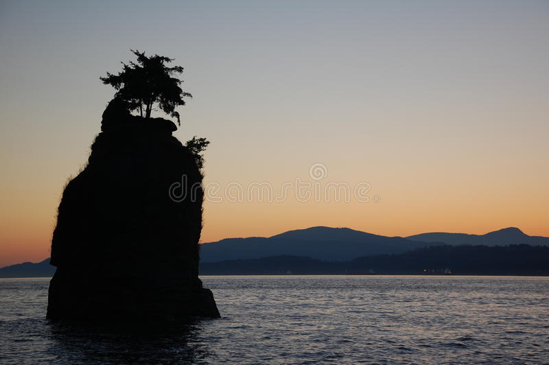 Silhouette d'une roche sur l'océan photos stock