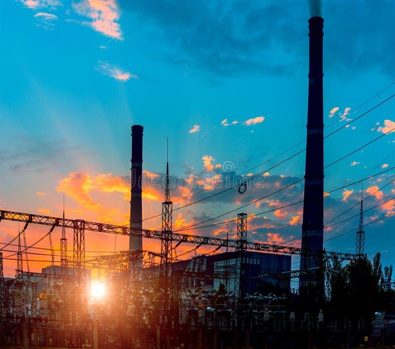Silhouette d'usine de courant électrique de turbine à gaz contre le coucher du soleil photos stock