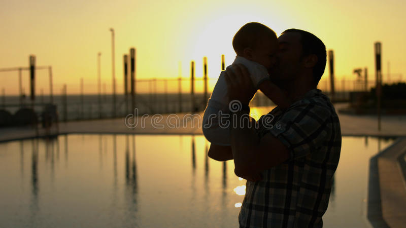 Silhouette of the the dad, who throws up his baby stock photo