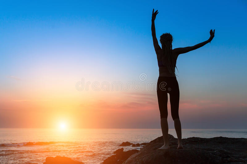 Silhouette of dancing slim woman on the ocean coast during an amazing sunset. Silhouette of dancing young slim woman on the ocean coast during an amazing sunset stock images