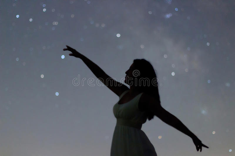 Silhouette of a dancing woman pointing in night sky. Woman Silhouette under starry night, Defocused Milky Way galaxy. Defocused night sky stock image