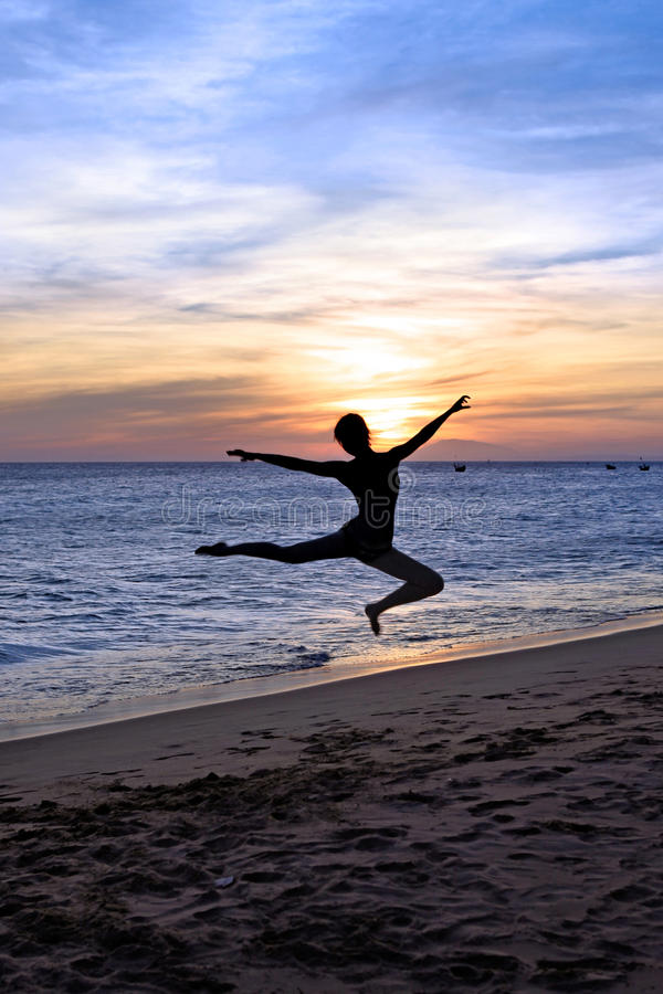 Silhouette dancing woman on the sunset. Silhouette dancing young woman on the beach. Sunset stock images